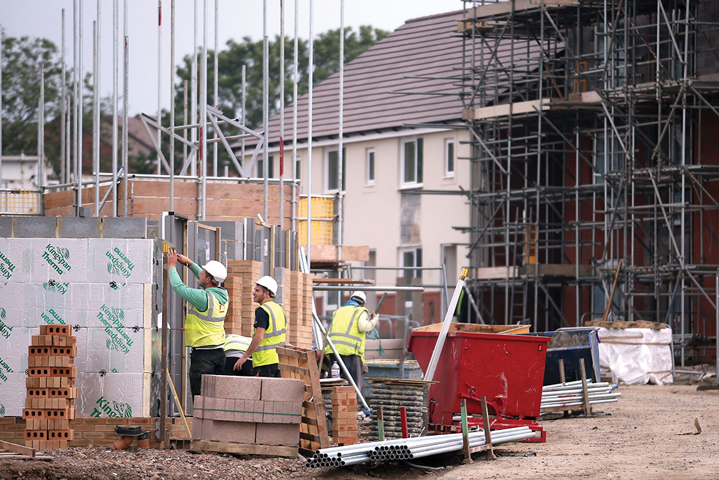 Construction workers build new houses in Bristol, England. The British construction industry provided plentiful employment for immigrants from Eastern Europe. [GETTY IMAGES]