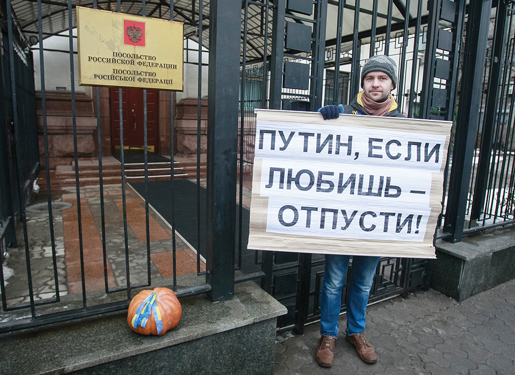 """A Ukrainian demonstrates against Russian involvement in Ukraine, holding a sign that says, """"Putin, if you love us, let us go!"""" in front of the Russian Embassy in Kiev in December 2013. The pumpkin is the symbol of a rejected marriage. [REUTERS]"""