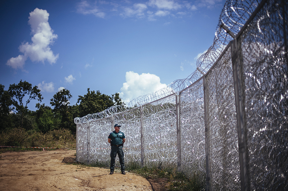 A border policeman stands next to a barbed wire wall on the Bulgarian border with Turkey, near the village of Golyam Dervent on July 17, 2014. Overwhelmed by an influx of mostly Syrian immigrants, Bulgaria has taken steps to secure its EU border -- including building a barbed-wire fence -- but now faces criticism from rights groups. The 30-kilometre (19-mile) fence, standing three metres (10 feet) high and fortified with razor wire coils, was completed this week. Covering the least visible section of Bulgaria's 275-kilometre (170-mile) border with Turkey, it aims to stem a flow of refugees that saw more than 11,000 people enter the country illegally last year -- 10 times the annual figure before the Syrian conflict.   AFP PHOTO / DIMITAR DILKOFF        (Photo credit should read DIMITAR DILKOFF/AFP/Getty Images)