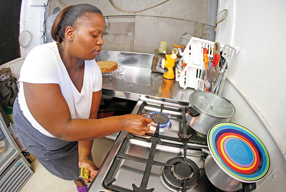 epa04623778 South African entrepreneur Nonny Mathildaseti lights a gas stove for cooking at Nonny's Bakery and Cafe in Masiphumelele, South Africa, 17 February 2015. Large scale industry as well as small businesses are feeling the pinch of South Africa's beleaguered state run power utility, Eskom. Eskoms inability to meet electricity demand has resulted in a tortuous schedule of rolling blackouts known as Load Shedding which is having a negative effect on the economy. Small businesses are adapting as best they can by switching to gas and adjusting product lines to cope with the regular power cuts. Load Shedding is expected to last several years until the poorly maintained power plants can return to full capacity and the new power plants are completed before proper service can resume to the country.  EPA/NIC BOTHMA