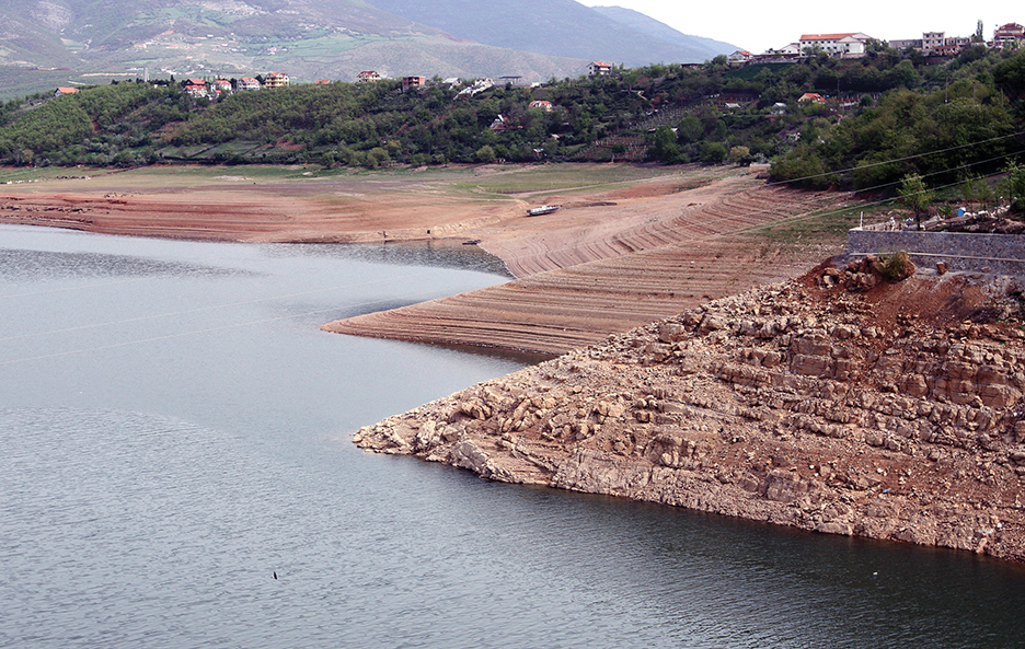 A boat is parked on the dry stretch of shoreline, which is normally covered by water, at the confluence of the White Drin and Black Drin rivers near northern Albania's town of Kukes April 9, 2014. Albania is working to arrange the import of electricity worth up to 90 million euros ($124.93 million) to make up for the loss of domestic output caused by a drought, officials said on Friday. The Balkan state, which relies almost entirely on hydro power plant to produce electricity, has seen water flows to its power stations cut by 40 percent in another year of little rain. To match ALBANIA-ELECTRICITY/  Picture taken on April 9, 2014.            REUTERS/Arben Celi (ALBANIA - Tags: ENERGY) - RTR3KWSC