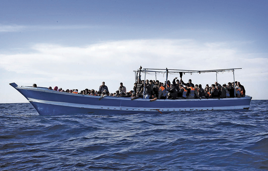 epa04183561 People on a boat carrying 267 migrants, including men, women and children, are pictured off the coast of Libya in the southern Mediterranean Sea, during the 'Mare Nostrum' operation by crew members of the Frigate 'Espero', 28 April 2014. According to recent reports, since 01 January, sea patrols have rescued about 22,000 migrants.  EPA/GIUSEPPE LAMI