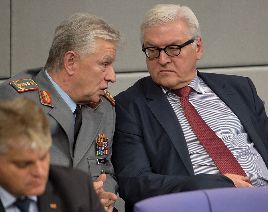 epa04515965 German Foreign Minister Frank-Walter Steinmeier (R) speaks with general Volker Wieker (C), Inspector General of the Bundeswehr, during the debate about the deployment of the German army in Afghanistan on occasion of the Mission Resolute Support (RSM) in the German parliament in†Berlin, Germany, 05 December 2014.  EPA/TIM BRAKEMEIER