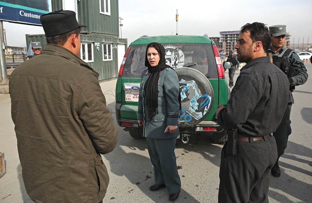 Afghanistan's first-ever female district police chief, Col. Jamila Bayaz, 50, center, talks to police at a check point in Kabul, Afghanistan, Thursday, Jan. 16, 2014. Afghanistan's first-ever female district police chief drew stares on Thursday as she drove and walked around the center of the city, reviewing check points and some of the important business and administrative facilities she is tasked with protecting. (AP Photo/Massoud Hossaini)