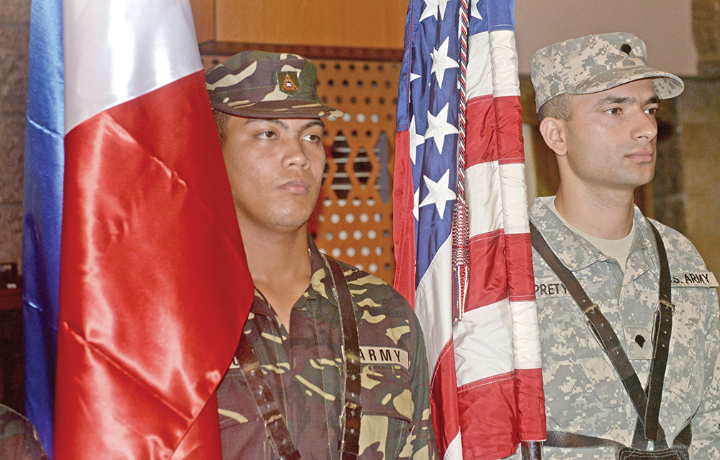 """Philippine (L) and US soldiers stand next there respective flags during the opening ceremony of the joint military exercise dubbed """"Balikatan 2015"""" at Camp Aguinaldo in Manila on April 20, 2015. The Philippines expressed alarm about China's reclamation activities in the disputed South China Sea as Manila launched war games with the United States to signal its intent to deter Chinese actions. AFP PHOTO / Jay DIRECTO (Photo credit should read JAY DIRECTO/AFP/Getty Images)"""