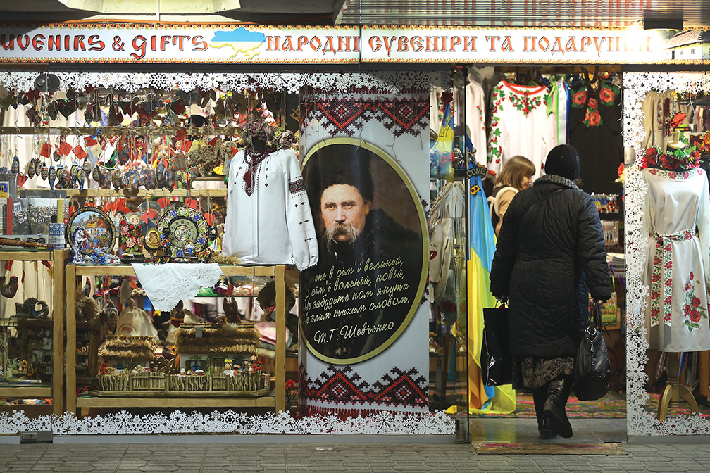 "KIEV, UKRAINE - FEBRUARY 21: A woman enters a shop selling Ukrainian ""national souvenirs"" and displaying a portrait of Ukrainian national poet Taras Shevchenko on February 21, 2015 in Kiev, Ukraine. Ukrainian nationalism and patriotism are both in common display in Kiev since the Crimea crisis last year. Fighting in the Donbas region of eastern Ukraine between pro-Ukrainian forces and pro-Russian separatists is continuing despite the recent Minsk ceasefire agreements. (Photo by Sean Gallup/Getty Images)"