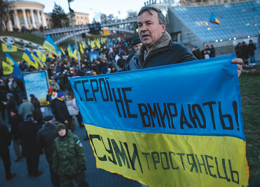 "A man holds a Ukrainian national flag as he takes part in a rally in central Kiev, November 21, 2014. Ukrainians marked the first anniversary of Ukrainian pro-European Union (EU) mass protests which caused a change in the country's leadership and brought Ukraine closer to the EU. The inscription reads, ""A hero never dies"". REUTERS/Gleb Garanich (UKRAINE - Tags: POLITICS ANNIVERSARY CIVIL UNREST) - RTR4F2X2"