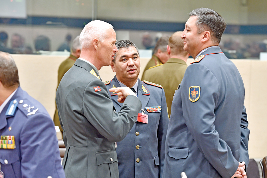 Ген.-лейт. Роберт Муд, военный представитель Норвегии в НАТО, слева, разговаривает с ген.-м. Бахтияром Сыздыковым и ген.-м. Муслимом Алтынбаевым из Казахстана на 173-й сессии Военного комитета НАТО на уровне начальников генеральных штабов в Брюсселе в мае 2015 г. НАТО