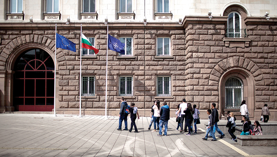 Люди проходят мимо флагов ЕС, Болгарии и НАТО в Софии после церемонии празднования десятилетия вступления Болгарии в НАТО, проходившей в апреле 2014 г. Болгария была одной из многих советских стран-сателлитов, стремившихся вступить в НАТО после окончания Холодной войны. РЕЙТЕР