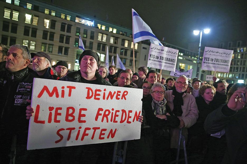 Люди принимают участие в ночном митинге, организованном мусульманскими группами около Бранденбургских ворот в Берлине в январе 2015 года в память о жертвах террористических атак в Париже. GETTY IMAGES