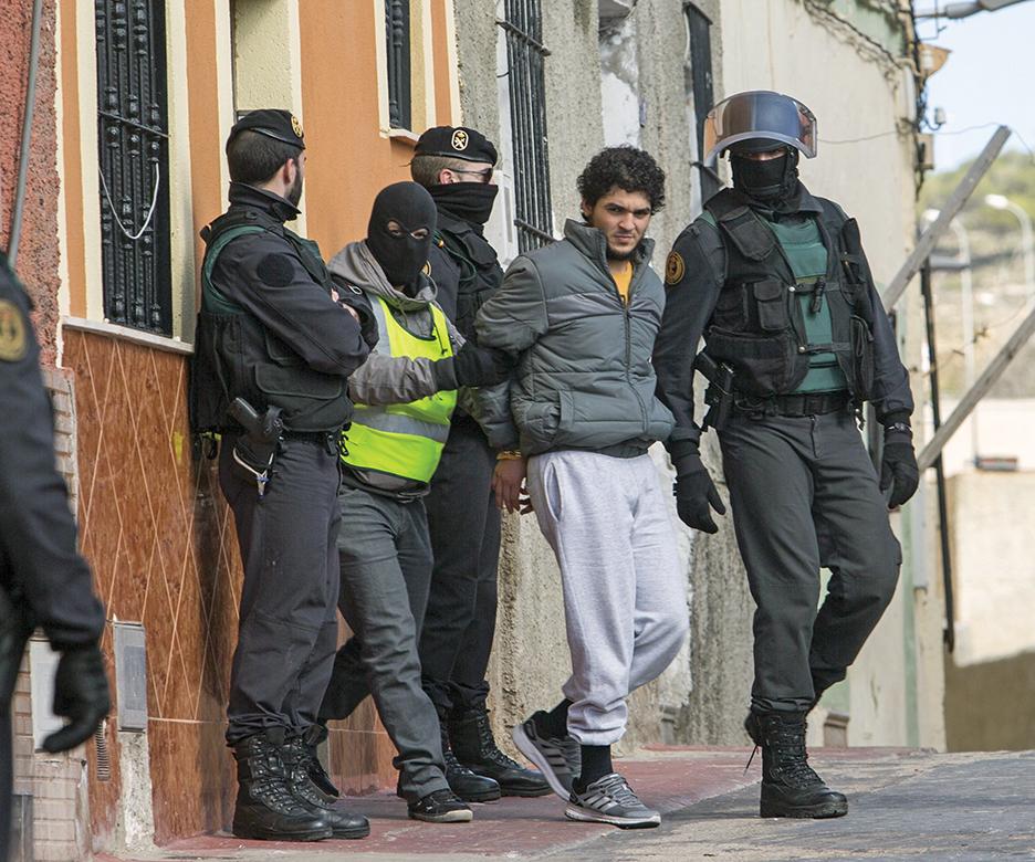 Сотрудники испанской Национальной гвардии в североафриканском анклаве Мелилья производят задержание мужчины, подозреваемого в использовании социальных сетевых ресурсов для вербовки новых членов в насильственные группы, такие как Исламское государство. AFP/GETTY IMAGES