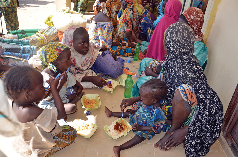Women and children eat at a Nigerian Army headquarters after being rescued from Boko Haram camps in Maiduguri, Borno State, in July 2015. AFP/GETTY IMAGES