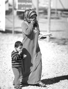 A displaced Iraqi woman forced from her home by jihadists walks with her son at the Harsham refugee camp west of Erbil in February 2015. AFP/GETTY IMAGES