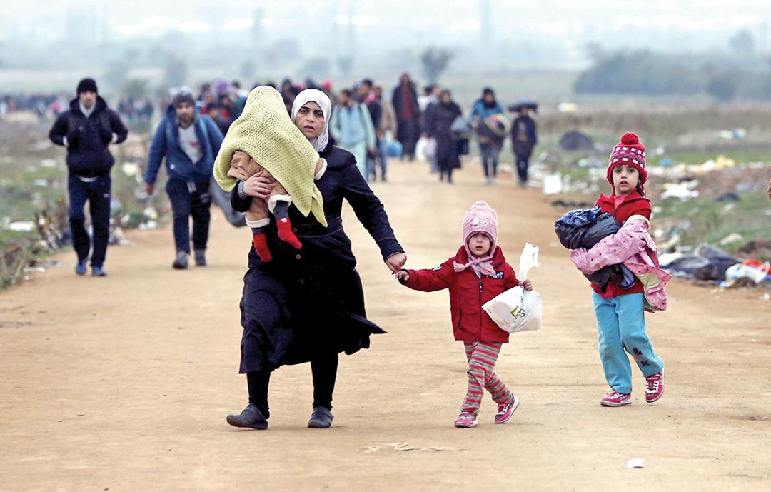 Мать-мигрантка со своими детьми идет пешком к сербской деревне после перехода границы с Македонией в октябре 2015 г. Женщины и дети сталкиваются с особыми трудностями на миграционных маршрутах. РЕЙТЕР