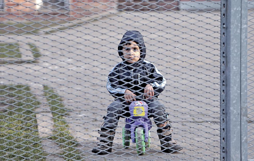 Ребенок-мигрант играет перед центром временного размещения мигрантов в Бела-Езове (Чешская республика, ноябрь 2015 г.). В ответ на критику Организации Объединенных Наций чешские власти перевели иммигрантов в более комфортные места для проживания. РЕЙТЕР