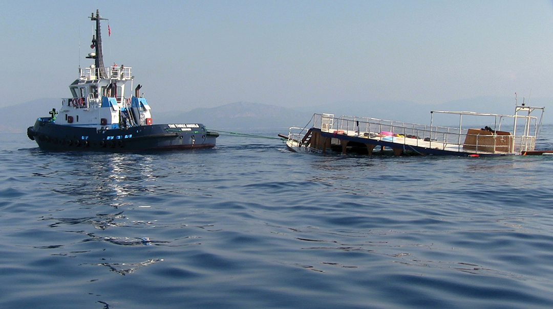 A sinking boat is towed to the Turkish shore in September 2015 after 22 migrants drowned in the Mediterranean Sea. [REUTERS]