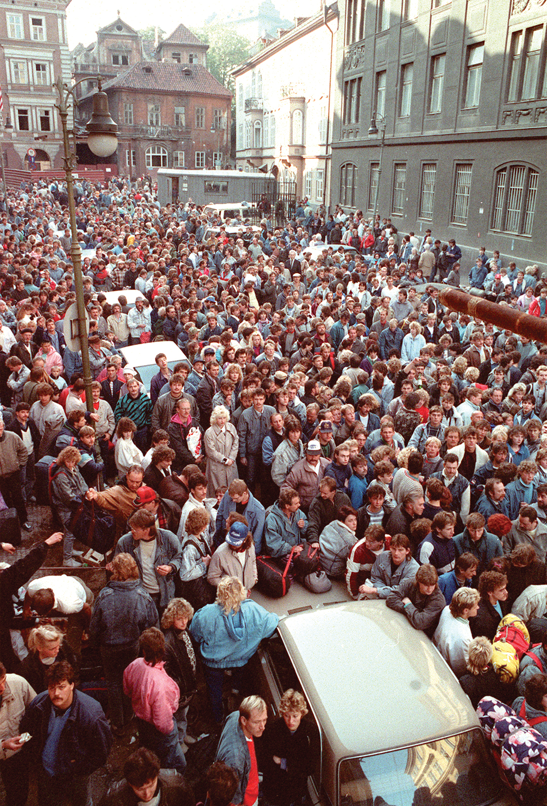 East German refugees penned behind barriers outside the West German Embassy in Prague in October 1989 wait to take a special train to West Germany after East Germany lifted restrictions on emigration. [AFP/GETTY IMAGES]