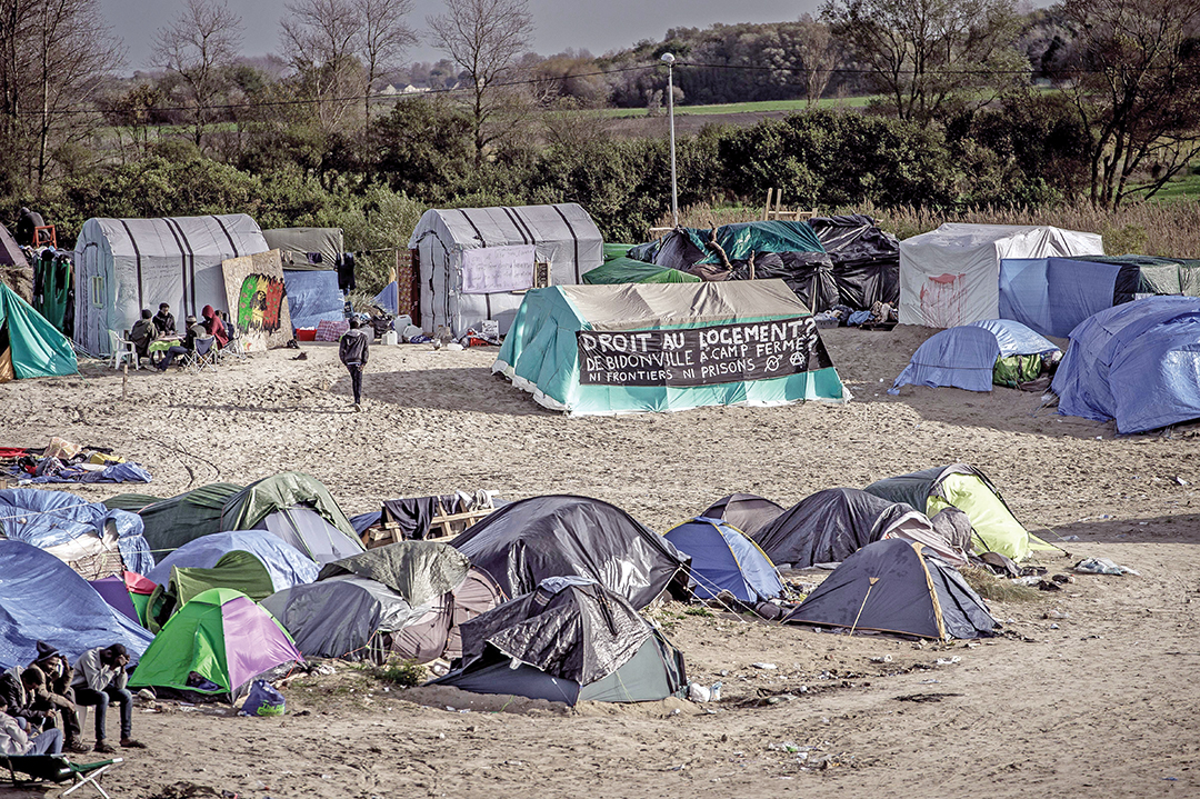 """Right to housing? From shantytown to closed camp? No borders or prisons,"" reads a banner in a migrant camp in Calais, France, in November 2015. A French court ordered the state to improve conditions at the giant ""New Jungle"" migrant camp after human rights activists complained. AFP/GETTY IMAGES"