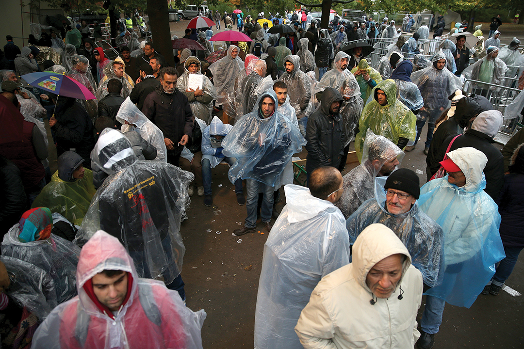 Migrants wait outside the central registration office for asylum seekers at the State Office for Health and Social Services in Berlin in October 2015. AFP/GETTY IMAGES