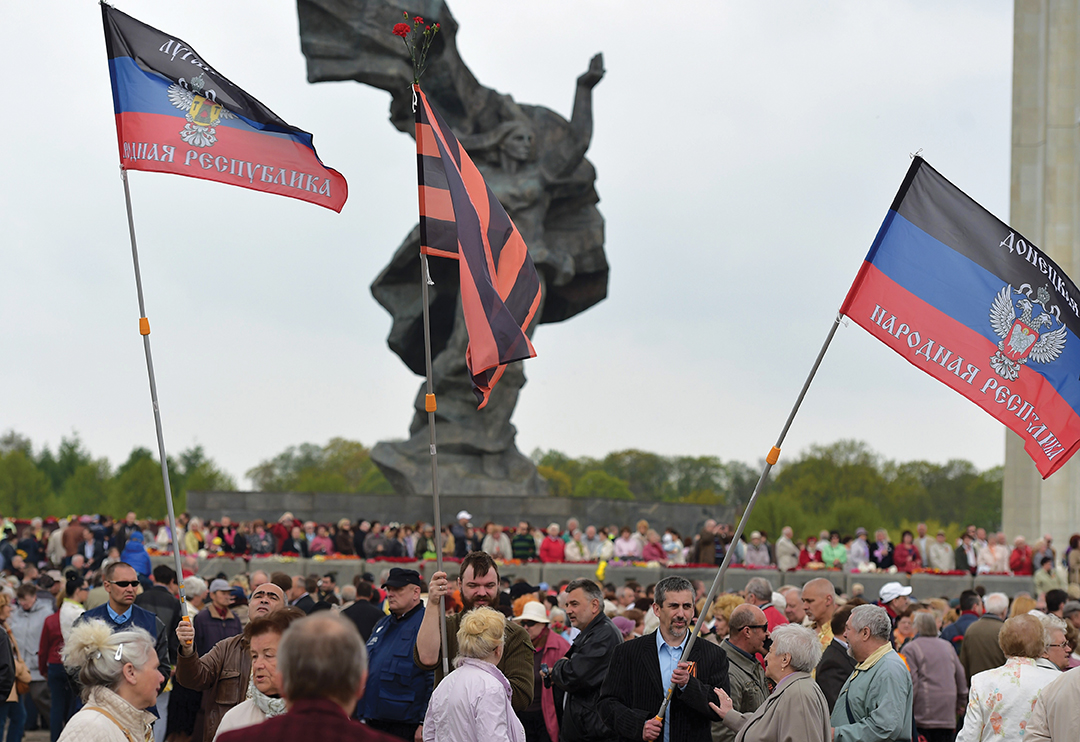 Pro-Russian activists wave flags of the Russian-backed rebels in eastern Ukraine during a gathering of Latvia's large ethnic Russian minority in Riga, marking an anniversary of the end of World War II. [AFP/GETTY IMAGES]