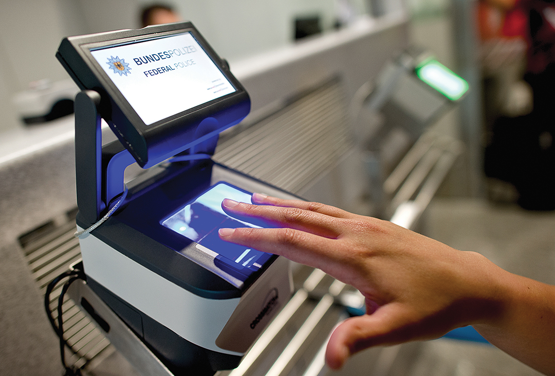 A female passenger scans her fingerprints as part of the Smart Border management system implemented at the airport in Frankfurt/Main, Germany, in June 2015. The EU Commission has launched a pilot project for checking non-EU citizens at the Frankfurt airport to help expedite border checks. EPA